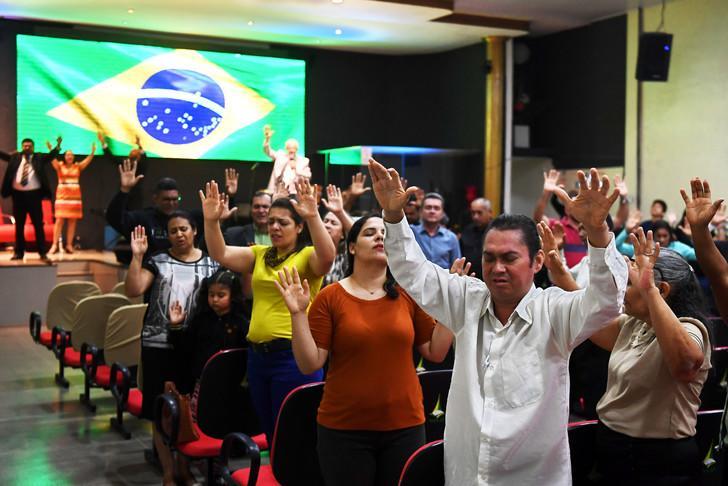 Evanjelikler, 21 Eylül 2018'de Brezilya da yapılan birinci tur cumhurbaşkanlığı seçimlerinin aşırı sağcı adayı olan Jair Bolsonaro'nun eski haline getirilmesi için kilisede dua ediyor - La Croix.jpg