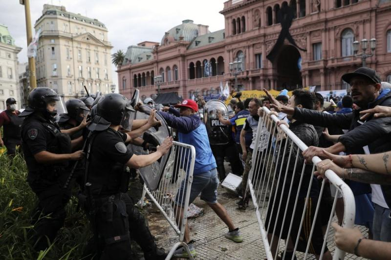 Başkanlık Sarayı önünde tabuta yaklaştırılmayan Maradona fanatiklerinin polisle çatışması.jpg