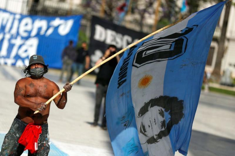 Başkent Buenos Aires'te  Maradona resmi ve forma numarası olan bayrakları sallayan bir taraftar_.jpg
