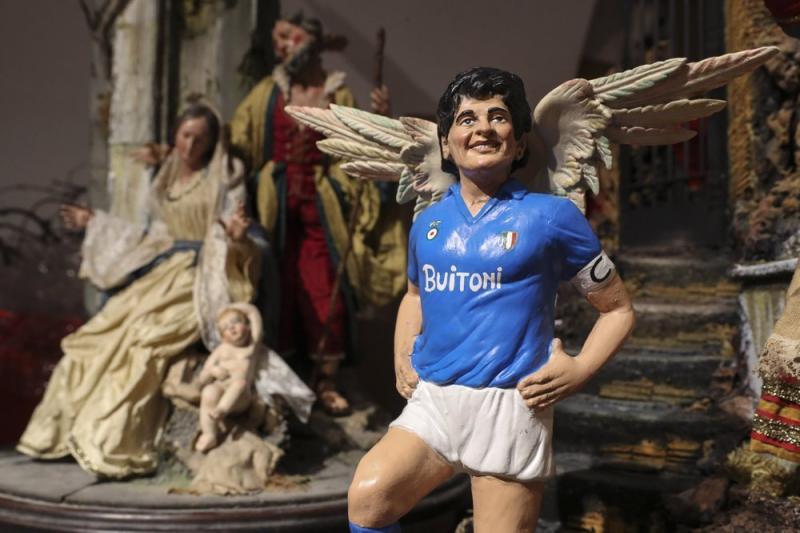 İtalya'nın Napoli şehrinde,ölümünden sonra  aziz ilan edilen çocuk Maradona heykeli, kilisede Meryem Ana ve meleklerle birlikte .jpg