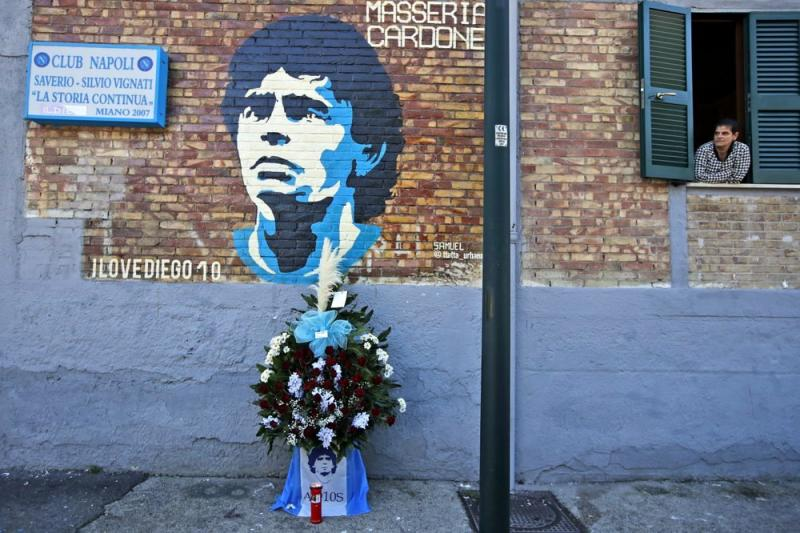 Napoli Spor Klübü tabelasının asılı olduğu duvardaki Maradona portrenin altına konulmuş veda çiçekleri .jpg
