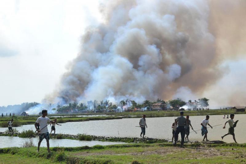 Haziran 2012'de yaşanan şiddet olayları sırasında silah taşıyan yerel Budistler yanan bir köyden uzaklaşıyor.  Fotoğraf İnsan Hakları İzleme Örgütü.jpeg