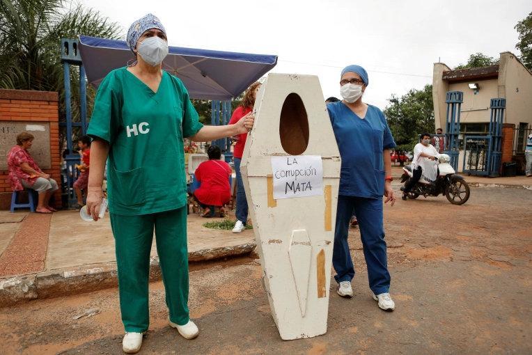 Hospital de Clinicas'ın sağlık çalışanları, San Lorenzo, Paraguay'da sağlık sisteminin çökmesini protesto ederken 'Yolsuzluk öldürüyor' yazan sahte bir tabutla ayakta duruyorlar Cesar Olmedo.jpg