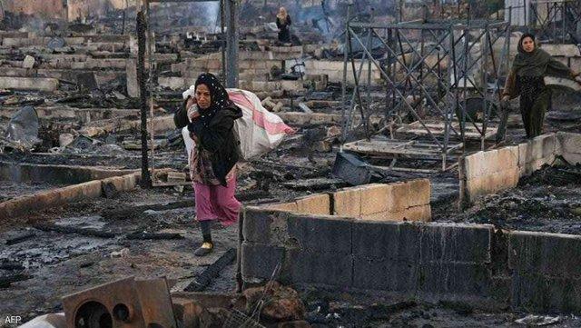 Yangından viraneye dönmüş mülteci kampını terkeden Suriyeli sığınmacı bir kadın-fotoğraf-AFP.jpg