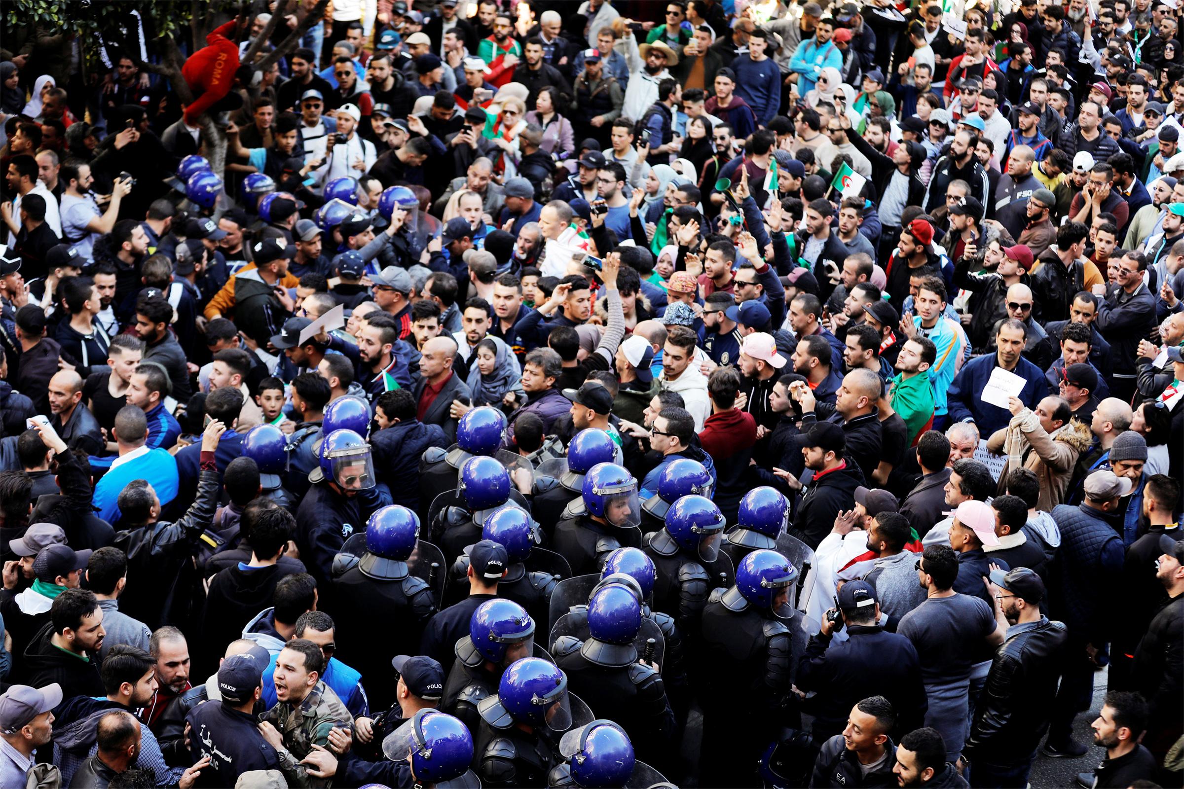 Polis memurları, Cumhurbaşkanı Abdelaziz Bouteflika'ya karşı düzenlenen bir protesto sırasında hükümet sarayına ulaşmaya çalışan insanları dağıtmaya çalışıyor.JPG