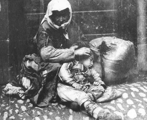 Ermeni anne ile çocuğu, bir bohçayla kaldırım kenarında oturuyorlar, 1918.jpg